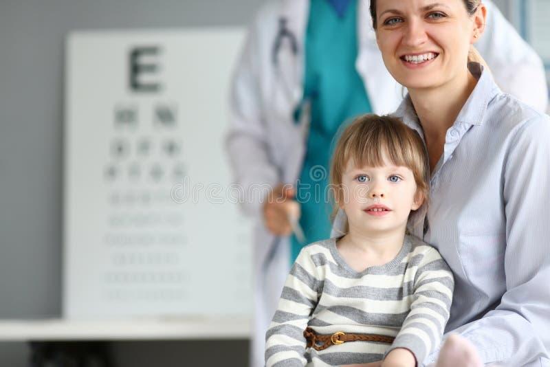 Familia sonriente feliz en la oficina del doctor del niño fotos de archivo