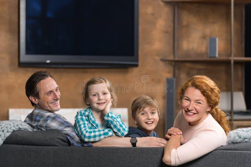 Familia sonriente feliz que se sienta en el sofá en sala de estar, pareja de los padres con dos niños imagenes de archivo