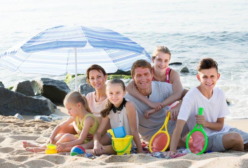 Familia sonriente grande de seis personas junto en la playa fotografía de archivo