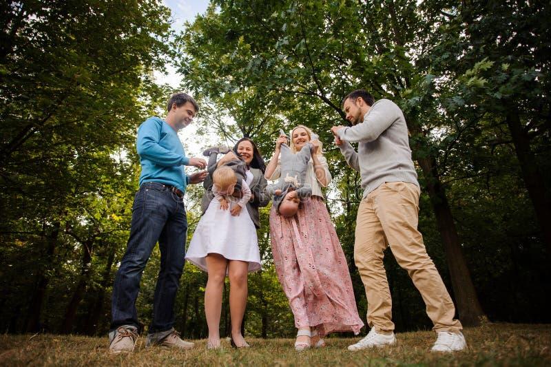 Familia sonriente grande y feliz que juega con los niños en parque imagen de archivo