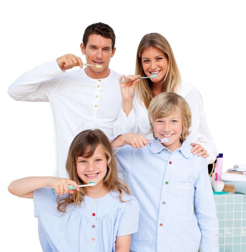 Familia sonriente que aplica sus dientes con brocha en el b imagenes de archivo
