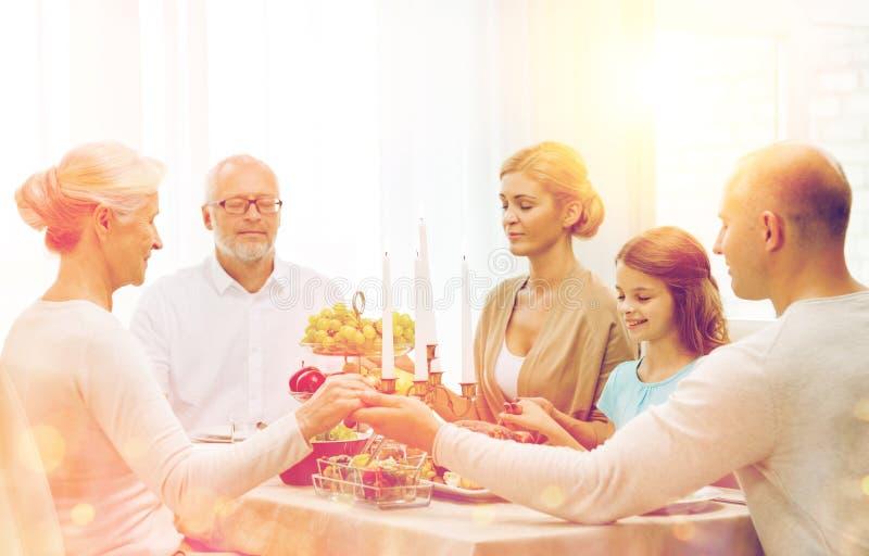 Familia sonriente que cena el día de fiesta en casa imagen de archivo libre de regalías