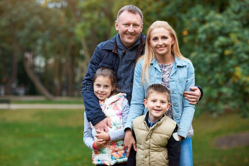 Familia sonriente que disfruta de un día del otoño en el parque imagen de archivo libre de regalías
