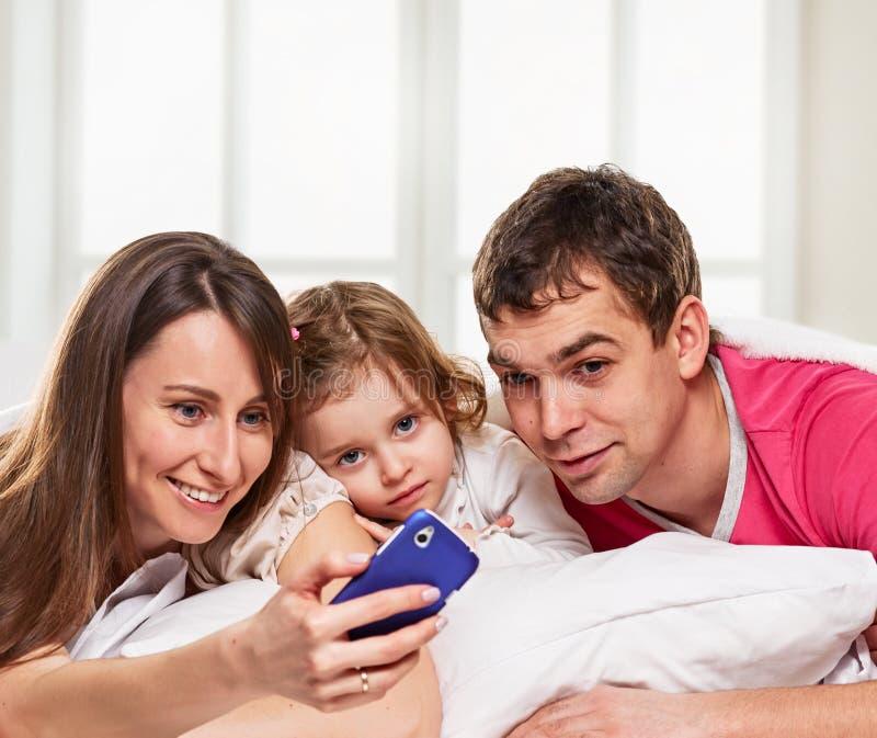 Familia sonriente que hace el hogar del selfie imagen de archivo