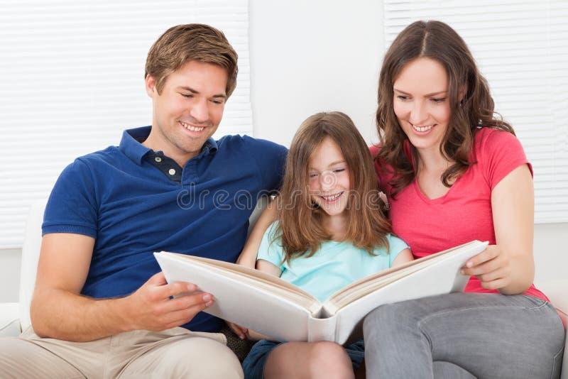Familia sonriente que mira el álbum de foto fotos de archivo libres de regalías