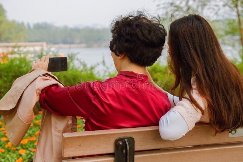 Familia, tecnología y concepto de la gente - hija feliz y madre mayor con el smartphone que se sienta en banco y tomar de parque imagen de archivo libre de regalías