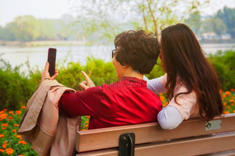 Familia, tecnolog?a y concepto de la gente - hija feliz y madre mayor con el smartphone que se sienta en banco y tomar de parque imagenes de archivo