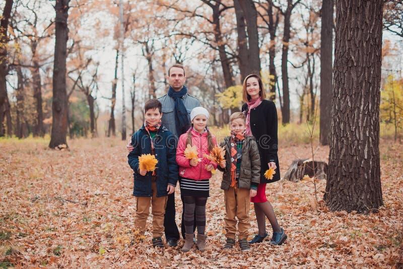Familia, tres niños en el bosque, permaneciendo en las hojas de otoño foto de archivo libre de regalías