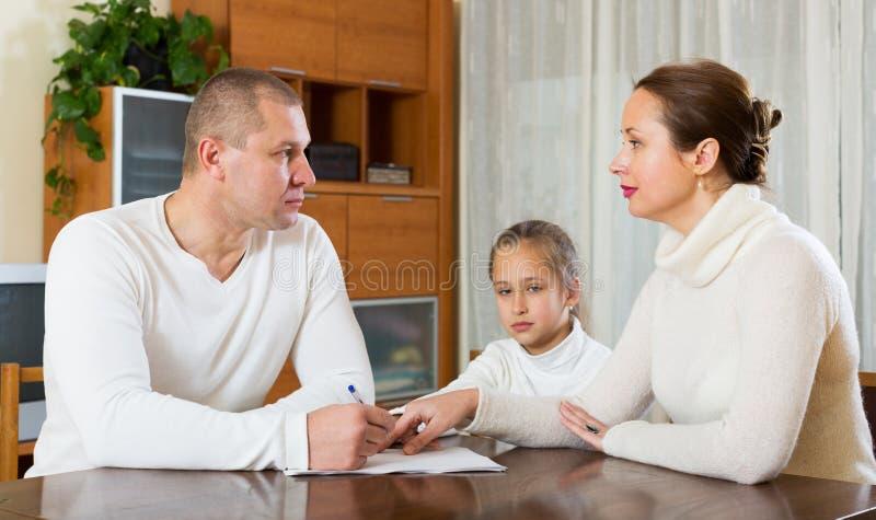 Familia triste de tres con los documentos imágenes de archivo libres de regalías