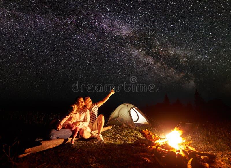 Familia turística con la hija que tiene un resto en montañas en la noche debajo del cielo estrellado con la vía láctea imagen de archivo