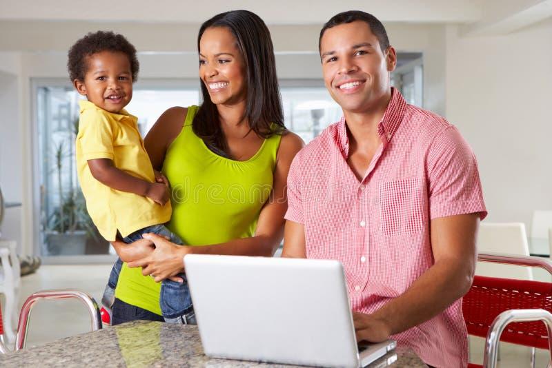 Familia usando el ordenador portátil en cocina junto imagenes de archivo