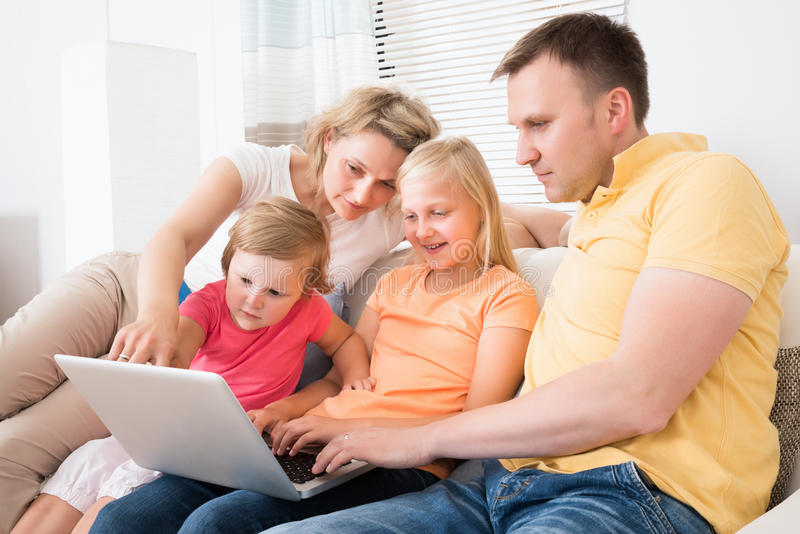 Familia usando el ordenador portátil en el sofá imagenes de archivo