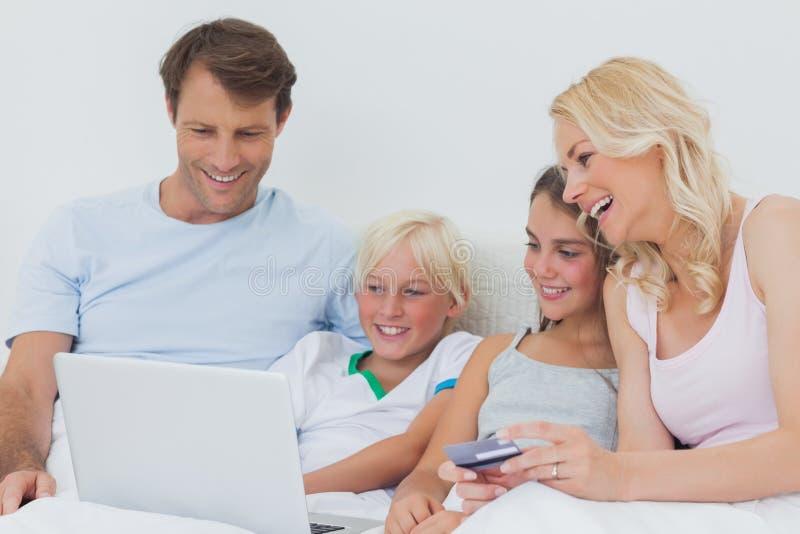 Familia usando el ordenador y tarjeta de crédito en cama imagen de archivo