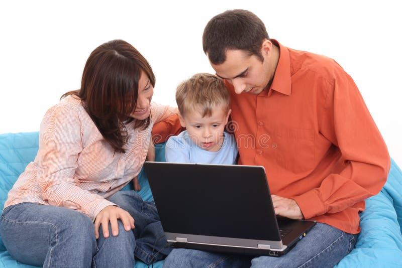 Familia usando la computadora portátil imagenes de archivo