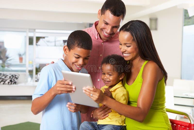 Familia usando la tableta de Digitaces en cocina junto imagen de archivo