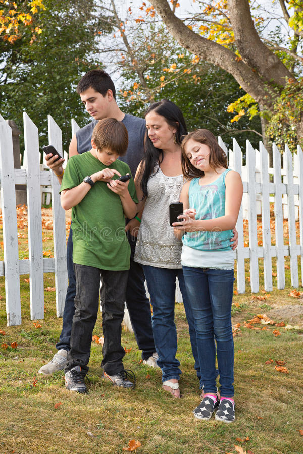 Familia usando los teléfonos celulares imagen de archivo