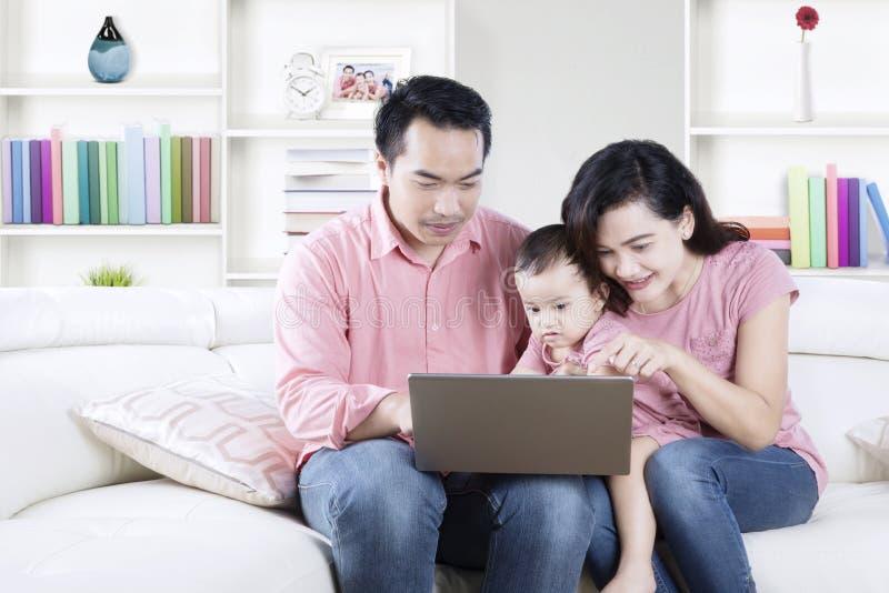 Familia usando un ordenador portátil en la sala de estar imagen de archivo