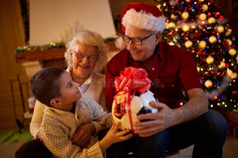 Familia víspera-sonriente de la Navidad que sostiene el regalo fotografía de archivo libre de regalías