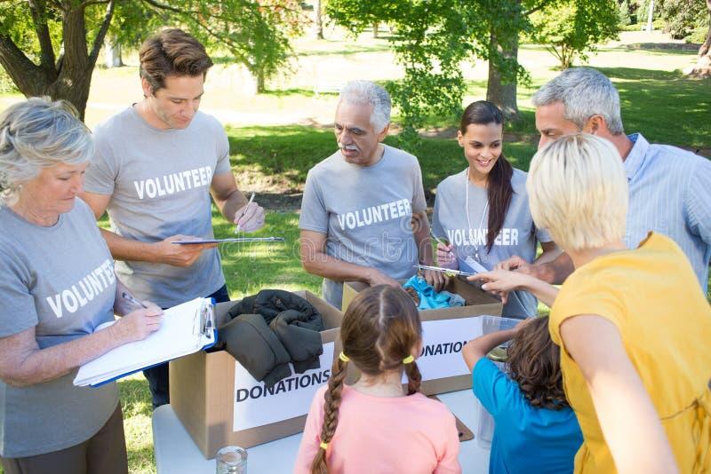 Familia voluntaria feliz que separa las materias de las donaciones fotos de archivo