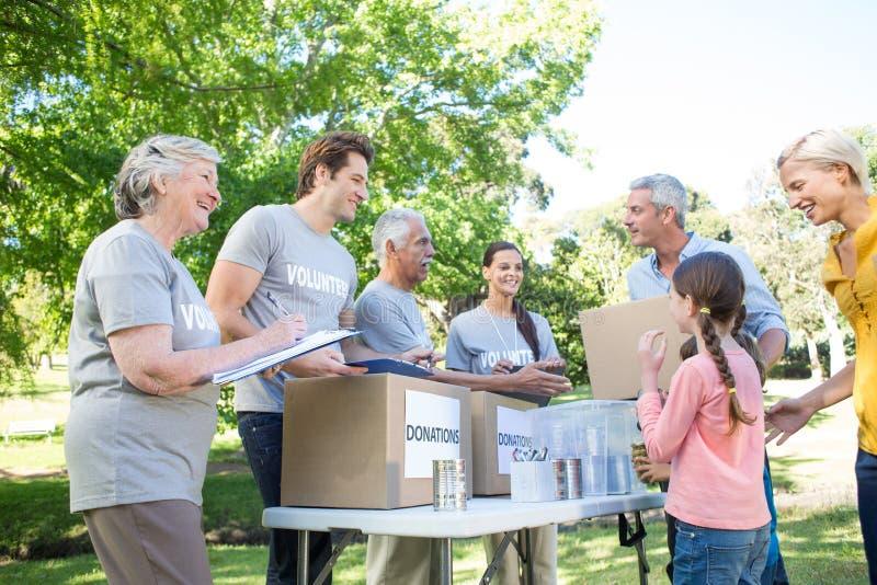 Familia voluntaria feliz que separa las materias de las donaciones imágenes de archivo libres de regalías