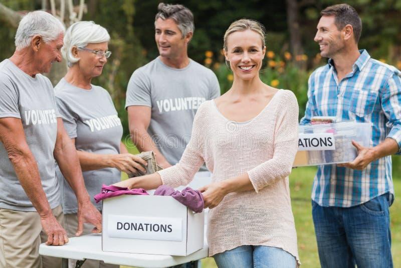 Familia voluntaria feliz que separa las materias de las donaciones imagen de archivo