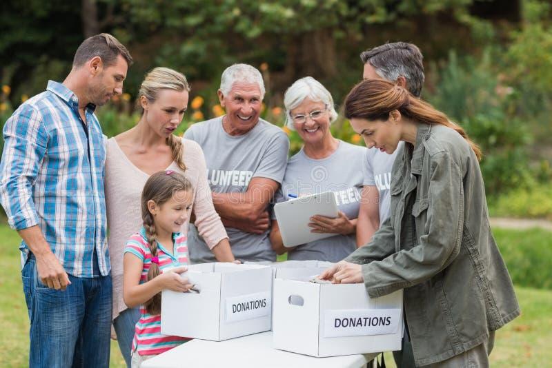 Familia voluntaria feliz que separa las materias de las donaciones fotografía de archivo libre de regalías