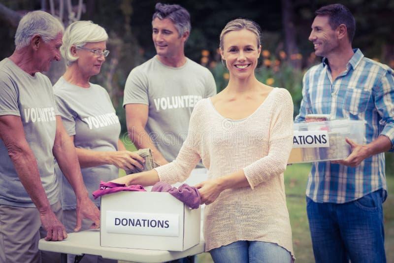 Familia voluntaria feliz que separa las materias de las donaciones fotos de archivo libres de regalías