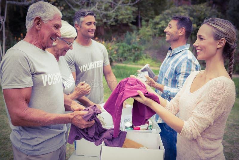 Familia voluntaria feliz que separa las materias de las donaciones fotografía de archivo