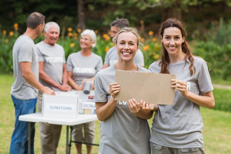 Familia voluntaria feliz que sostiene las cajas de la donación imágenes de archivo libres de regalías