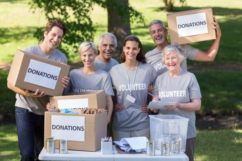 Familia voluntaria feliz que sostiene las cajas de las donaciones imagen de archivo