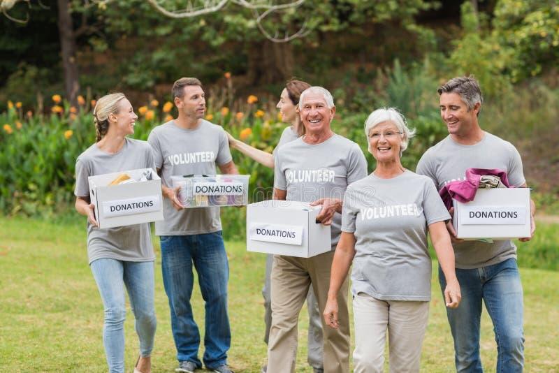 Familia voluntaria feliz que sostiene las cajas de las donaciones fotos de archivo libres de regalías
