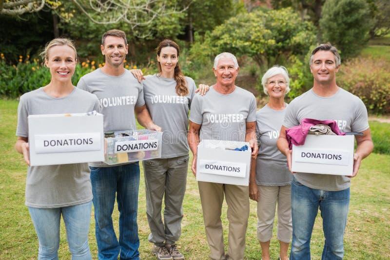 Familia voluntaria feliz que sostiene las cajas de las donaciones foto de archivo