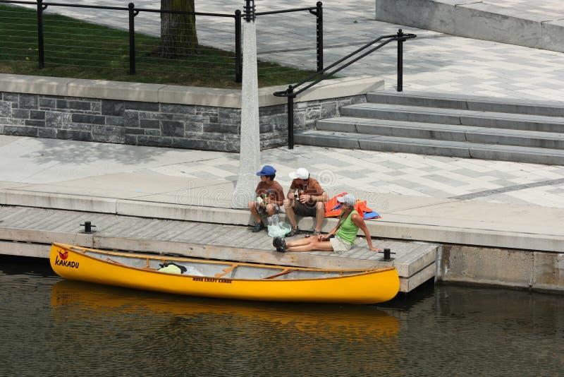 Familia y canoa amarrada foto de archivo