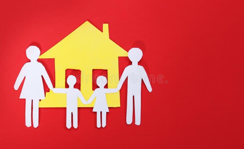 Familia y casa de papel sobre fondo rojo. Concepto. foto de archivo