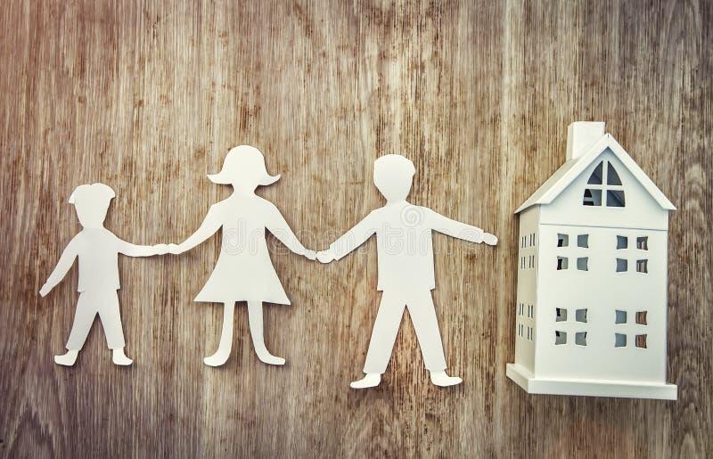 Familia y concepto casero Padre, madre de papel e hijo llevando a cabo las manos cerca de casa miniatura en fondo de madera fotos de archivo