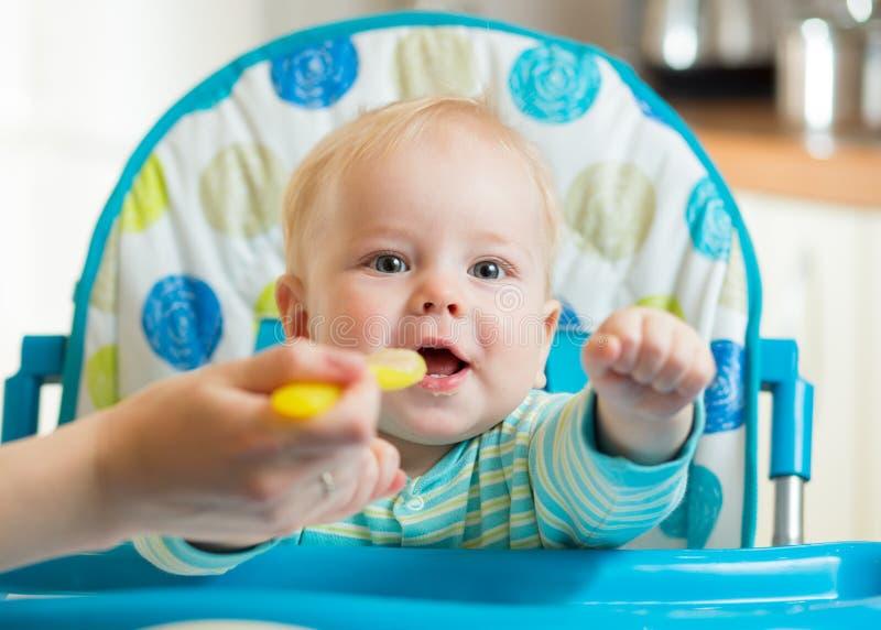 Familia y concepto de la nutrición - mime a la cuchara que alimenta al pequeño bebé que se sienta en highchair en casa imagenes de archivo