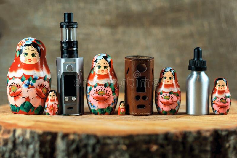 Familia y e-cigarrillo de Matryoshka Cosas de Vaping y muñeca rusa en una tabla de madera Vape de Rusia fotos de archivo libres de regalías