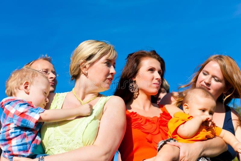 Familia y multigeneración - diversión en prado en verano imagen de archivo