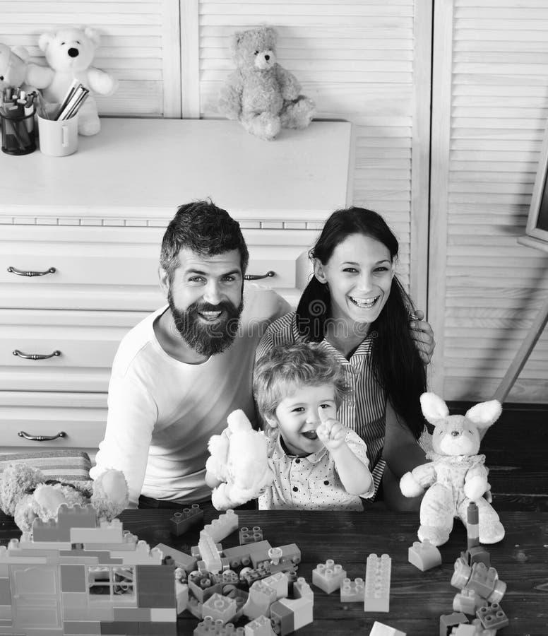 Familia y niñez La mamá, el papá y el muchacho juegan con los juguetes foto de archivo libre de regalías