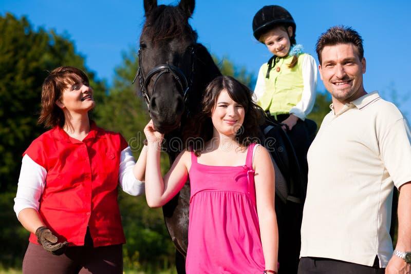 Familia y niños que presentan con el caballo imagenes de archivo