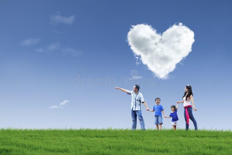 Familia y nube felices del amor en parque fotos de archivo