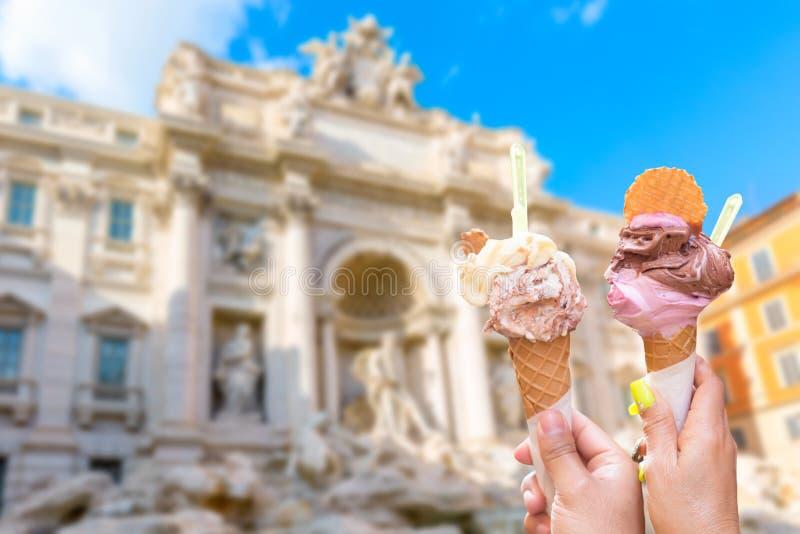 Familiar chountain di Trevi em Roma, Itália durante o dia ensolarado de verão com gelato de gelado italiano em primeiro plano foto de stock royalty free