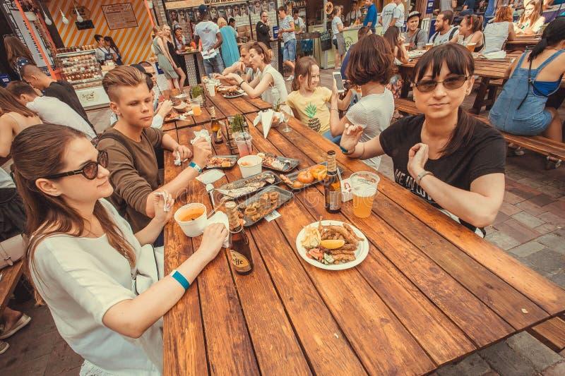 Familias con los niños adolescentes que cenan, comiendo y bebiendo durante festival al aire libre de la comida de la calle imagen de archivo libre de regalías