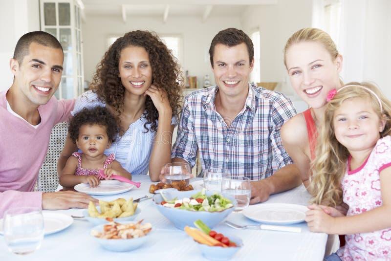 Familias que disfrutan de la comida junto en casa imagenes de archivo