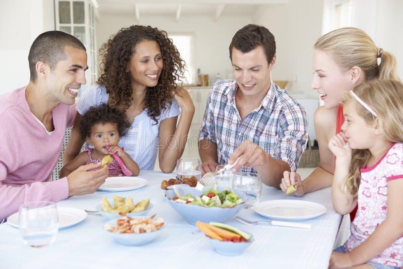 Familias que disfrutan de la comida junto en casa imagen de archivo