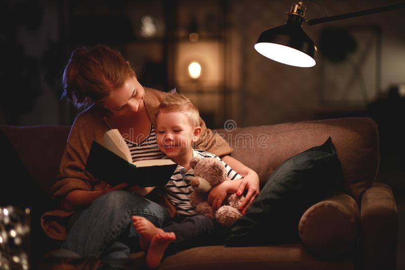 Familie alvorens de naar bed te gaan moeder aan haar boek van de kindzoon dichtbij een lamp in de avond leest royalty-vrije stock afbeelding