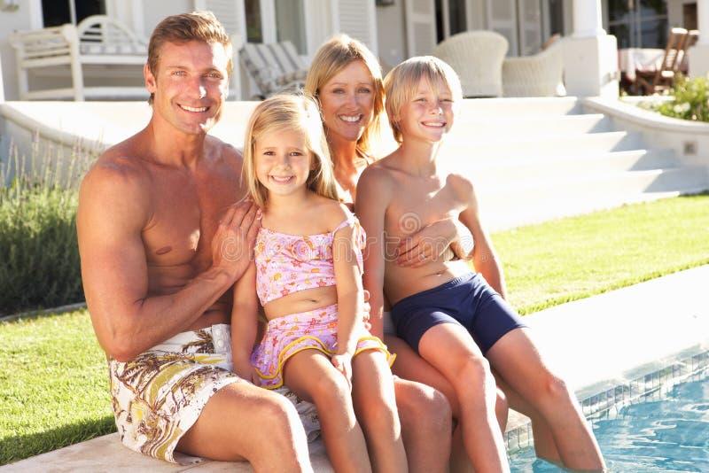 Familie außerhalb der Entspannung durch Swimmingpool stockbild