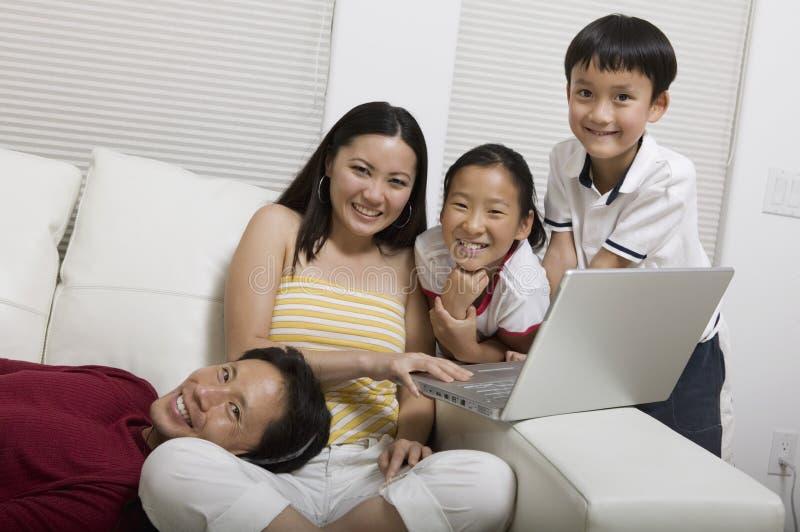 Familie auf Couch unter Verwendung des Laptopporträts lizenzfreie stockfotografie