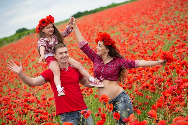 Familie auf dem Mohnblumenfeld stockbild