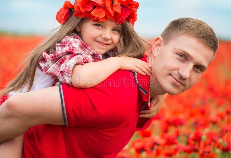 Familie auf dem Mohnblumenfeld lizenzfreie stockbilder